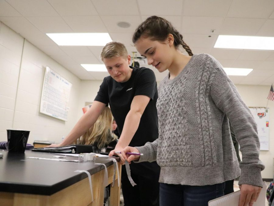Sophomore Avery Logan and junior Chase Poulson participate in the sticky tape lab for chemistry. Chemistry students tested materials reaction to charged pieces of tape.
