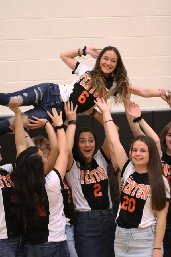 Being lifted up by her teammates, senior Hannah Clarke poses for a funny picture. The varsity soccer team took pictures at the annual spring meet the team on March 20.