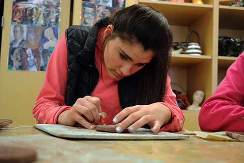 Carving a quote into her clay, junior Sydney Cuneaz focuses on her work. The class was engraving clay circles to turn into magnets.