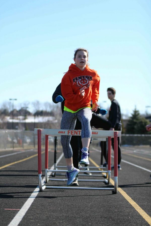 Junior Drew Follett keeps her eyes focused ahead as she leaps over the last hurdle. The track team practices for their first meet of the season on April 18 at Flushing at 4 p.m..