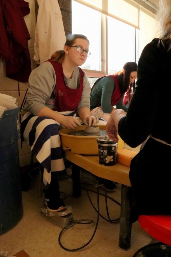 Sophomore Katelyn Dobbs sits behind the pottery wheel making a clay bowl, with the assistance of art teacher Teresa Moss. Sculpture and drawing is working on individual projects.