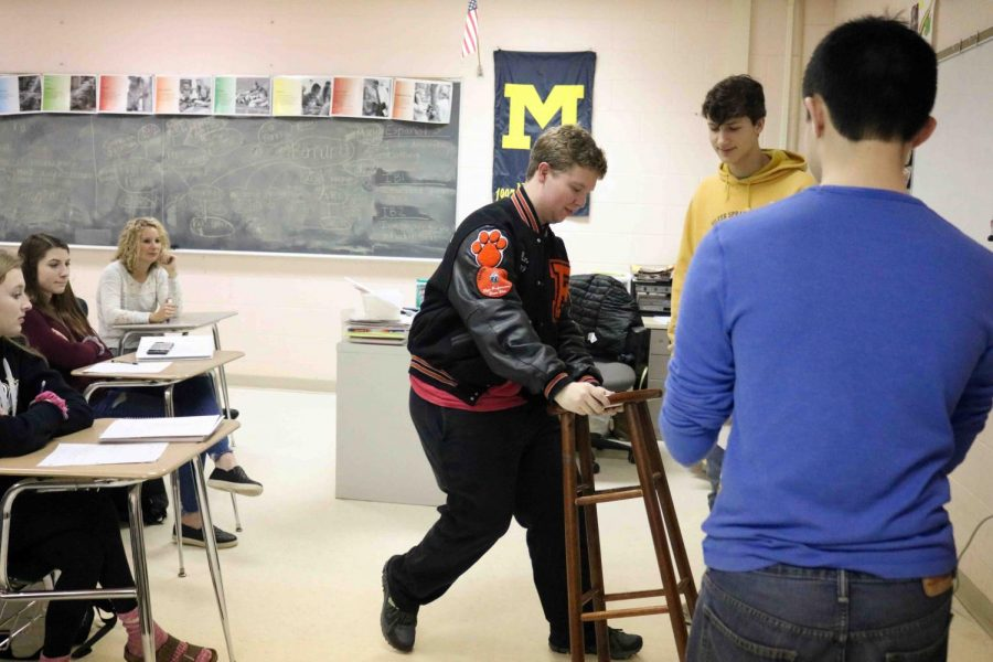 Junior Ben Siemiantkowski grabs a stool to help set up a Spanish presentation. The Spanish kids had to describe two outfits for their clothing unit projects they made in class.