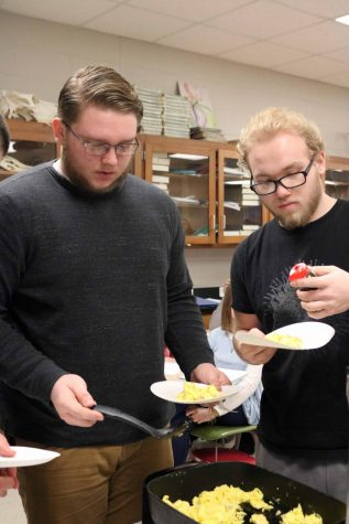 Junior Logan Prater scoops scrambled eggs and sheep brains onto his paper plate.  The anatomy classes dissected a sheep's brain and Anatomy teacher Lisa Stewart cooked it for her classes to eat.