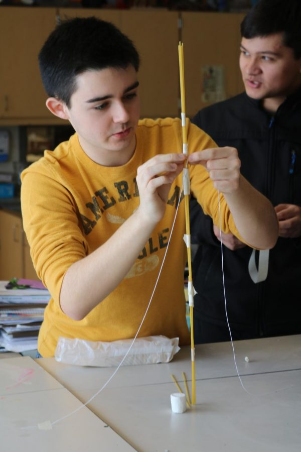 Trying to win first place, sophomore Ryan Pearce focuses on taping string to support his spaghetti structure. CADD teacher, Andy Cocagne hosted a contest for his students to see who could build the highest structure to support a marshmallow.