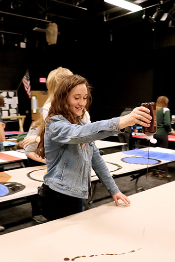 Squirting the paint on her paper, sophomore Taron Masi paints her back drop. In her drama class, they are painting their own backgrounds for their story.
