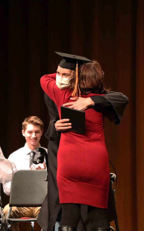 After receiving his diploma, senior Kyle Gauer hugs his teacher. The high school hosted an early graduation ceremony for Kyle and his family.