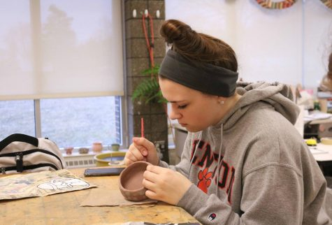 Junior Alaina Russo, works on her sgraffito bowls in her art class. The art students were asked to make bowls and paint an iron oxide slip over them and then to scratch through the slip layer to create a pattern, these bowls will be sold at the art show held at AGS middle school.