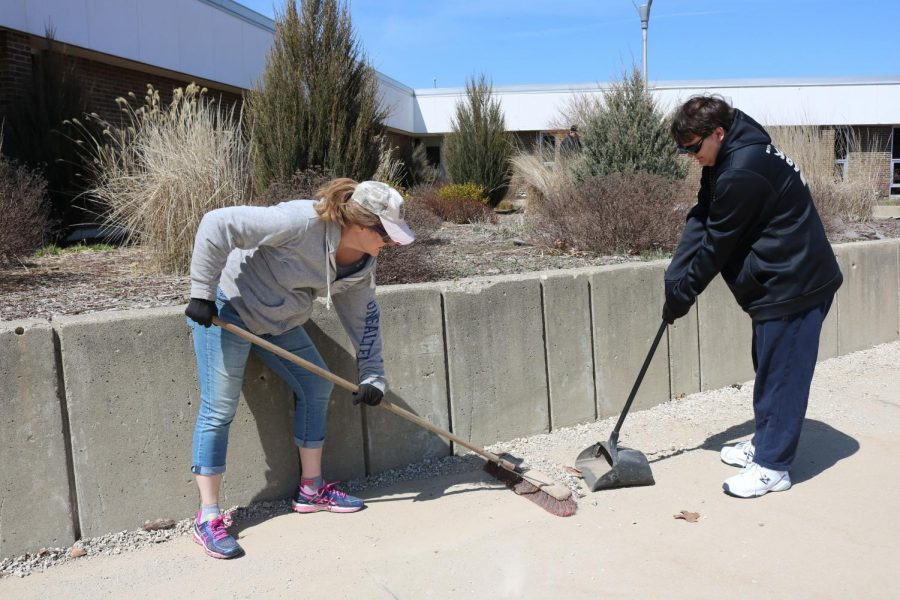 Sophomore Alex  Thompson helps his mom clean up around the school. On Apr. 22, students cleaned up the school grounds to celebrate Earth Day.