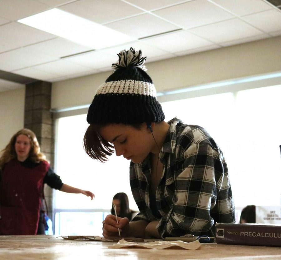 Junior Isabelle Geurtin is carving shapes and patterns into her clay bowl. Theresa Moss' sculpture and design class has been working on clay bowls for a few weeks. They make the shape of the bowl on the pottery wheel, bake and glaze them, then carve designs into the sides with clay tools.