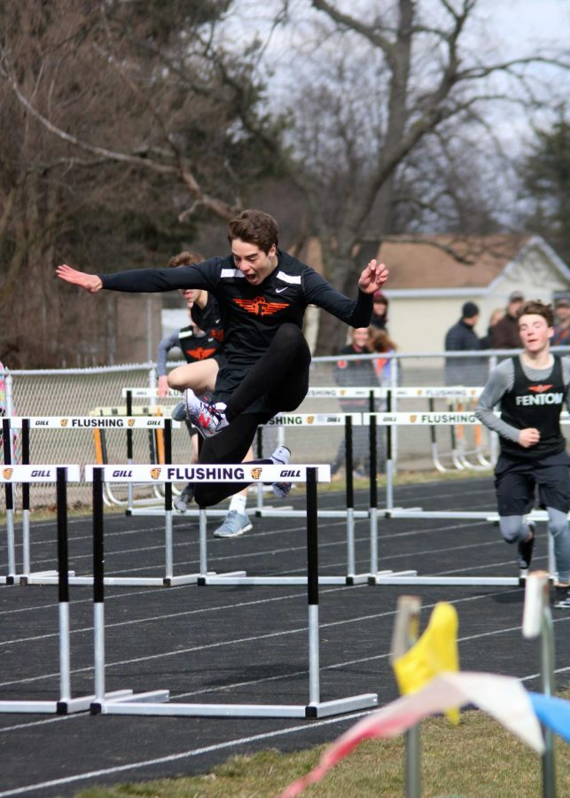 Leaping over a hurdle, junior Gabe Horton pushes toward the finish lines to come first in the 100 meter hurdles. The track team competed at Flushing High School against Swartz Creek and Flushing on April 18.