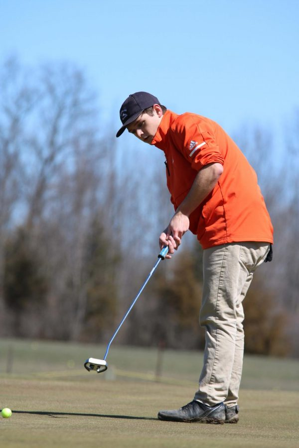 Senior Tait Shaltz putts his second hole of the match against Owosso on Apr. 20. The varsity team won 215-171.
