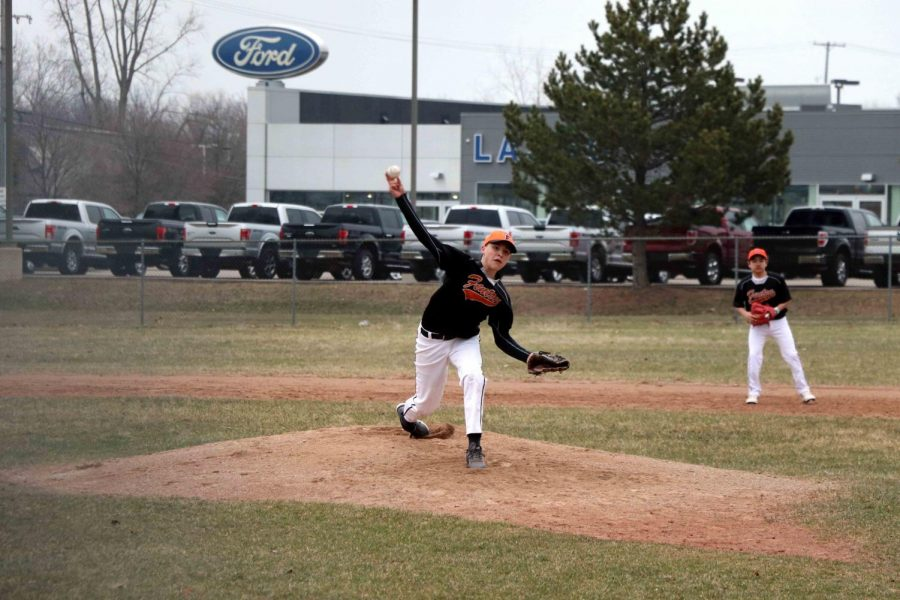 Playing in the first game of the season, freshman Jake Wohlfert pitches to the opposing team. After winning their first game against Flushing with a score of 12-2, the team's second game was cancelled due to the poor weather conditions.