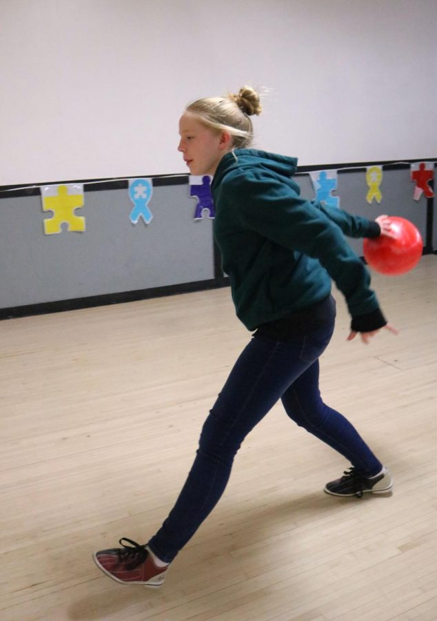 Freshman Andrea Elsholz tosses a bowling ball during a game of bowling with fellow soccer players. On Apr. 13, the girls soccer team hosted a fundraiser at Holly Lanes to raise money for medical research.