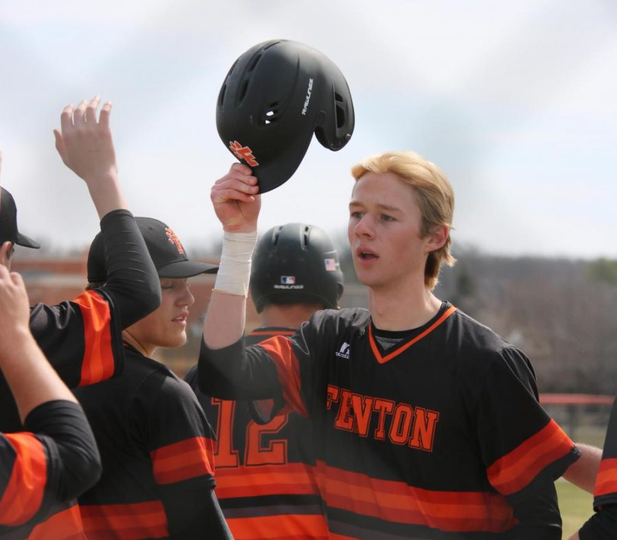 Senior Nolan Lawrence high fives his teammates after scoring a run on April 21. The boys played Waterford-Kettering and lost 9-7.