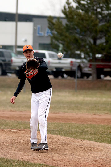Catching the ball, Freshman Jake Wohlfert pitches for his team.  The boys played a double header winning the first game 12-2 and  cancelling the second due to the rain.