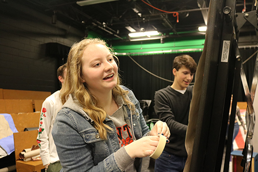 Preparing for her drama skit, sophomore Anna Avendt tapes up her backdrop. Drama students were in charge of painting their own scenery for this assignment.