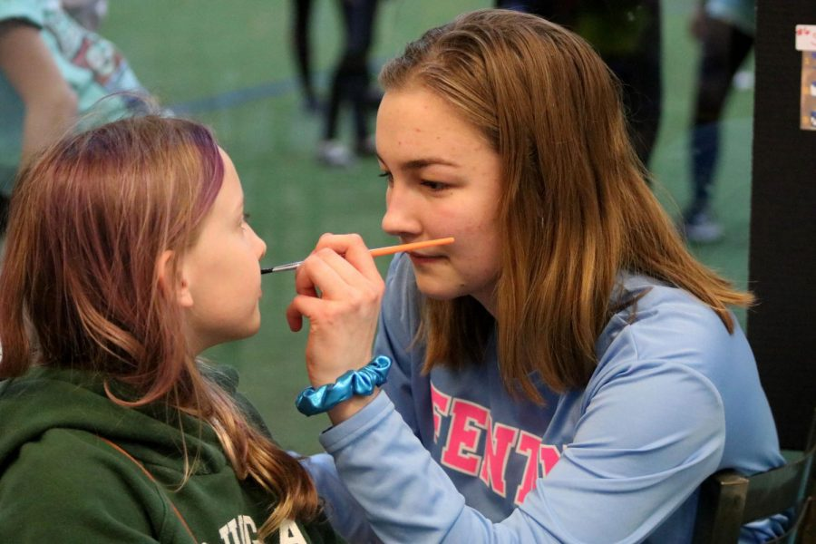 Junior Lucy Muesch painting kids faces at Sports lab in Fenton on Torrey road. Varsity girls Soccer has a home game Monday April 30th.