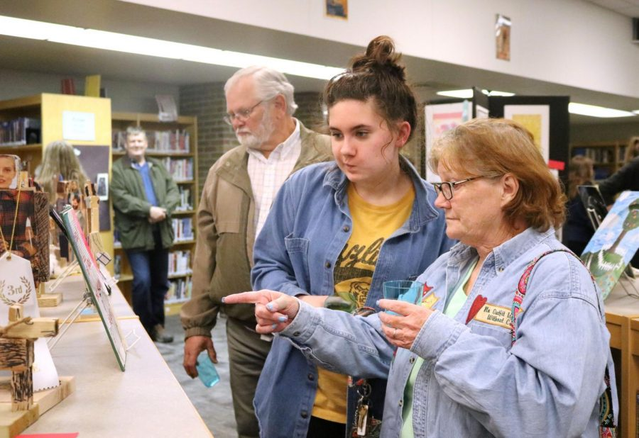 Freshman Sophie Swift looks at a piece of artwork with her grandmother on Apr. 26. The annual art show was held in the media center where students won prizes for their work.