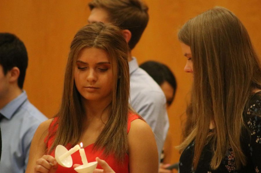 Sophmore Maria Ebert passing off a flame to fellow inductee sophmore Sarah Dziadzio. The National Honors Society Induction was held on April 25th in the main gym.
