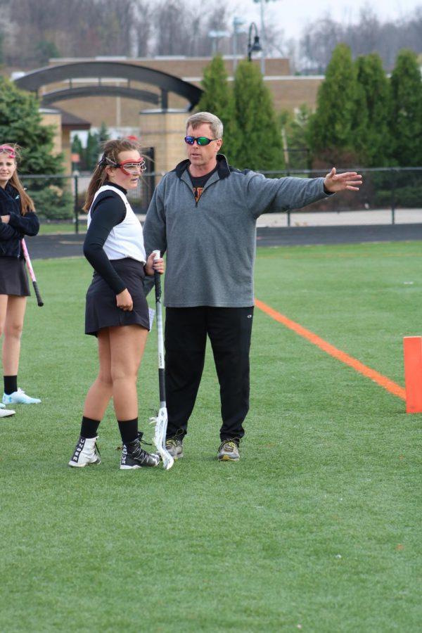 Coach Roger Ellis gives senior Kelly Kemp some instruction on the sideline.