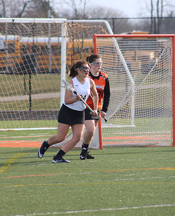 Preparing to catch a pass, freshman Lydia Anderson attempts to outrun her opponent. The varsity girls lacrosse team beat the Flushing Raiders 14-7.