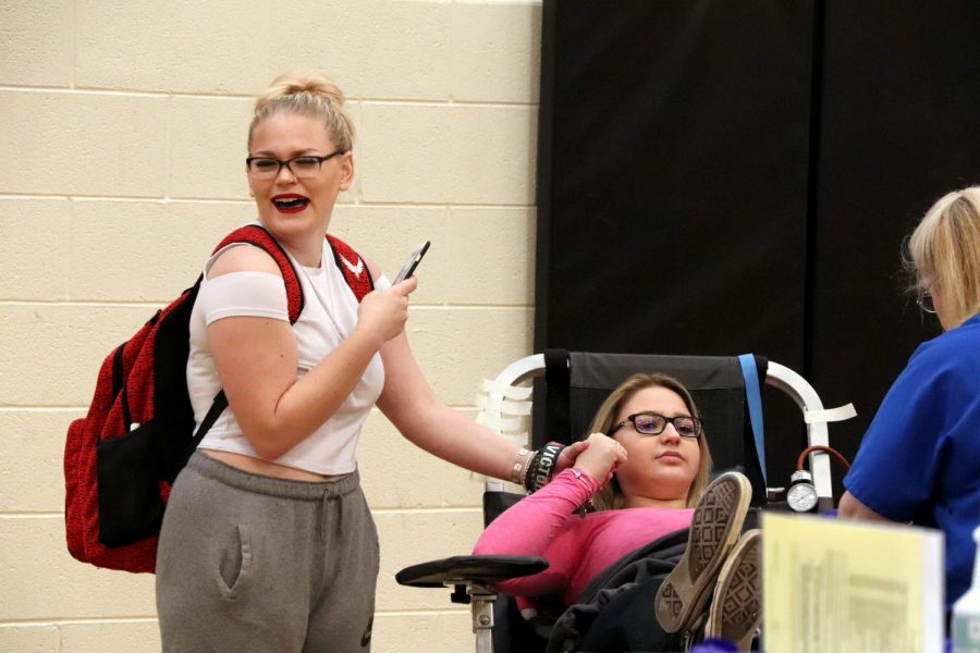Sophomore Lauren Bacon holds sophomore Olivia Miller's hand as she donates blood. The blood drive took place on Tuesday, April 17.