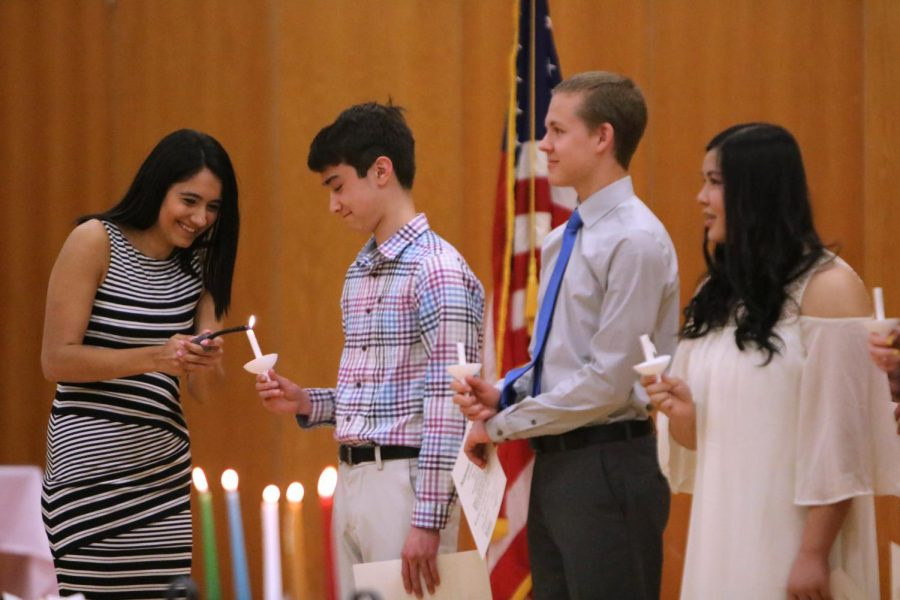 New inductees sophomores Nathan Klump, Jake Kennedy and Lily Huynh passes the candle flame to the new National Honor Society members. Fenton High welcomed 53 members to the club.
