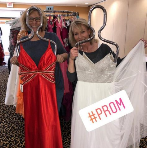 Volunteers and young ladies hold up dresses donated to ROCKit.