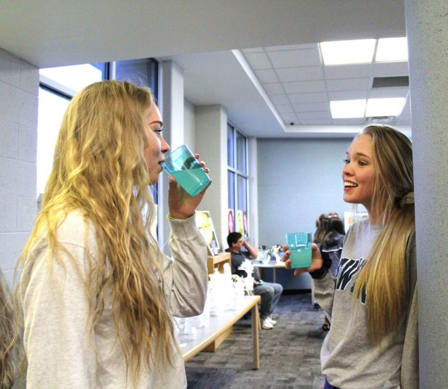 Senior twin sisters, Sarah and Chelsea Barnett enjoy beverages while at the art show put on by all of the art classes. Students had their art evaluated by a panel of judges.