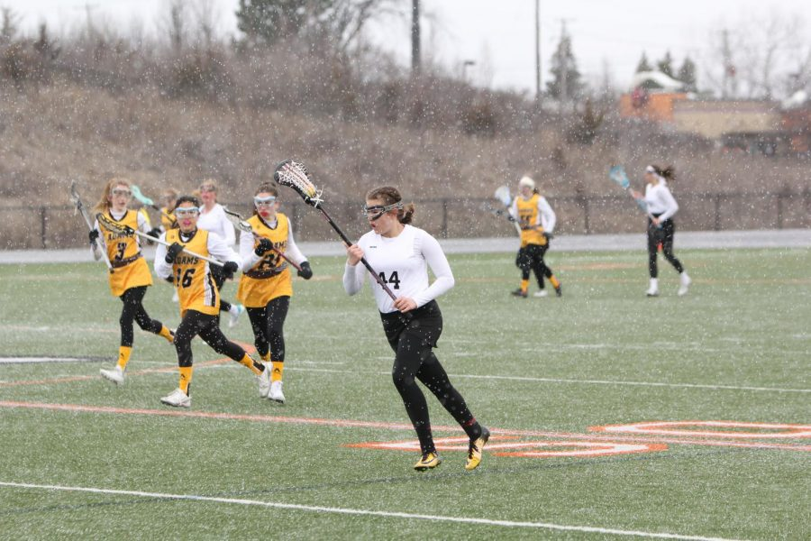 Freshman Emilee Guertin runs the ball down the field during a hail storm. Flax lost 15 - 1 against Adams