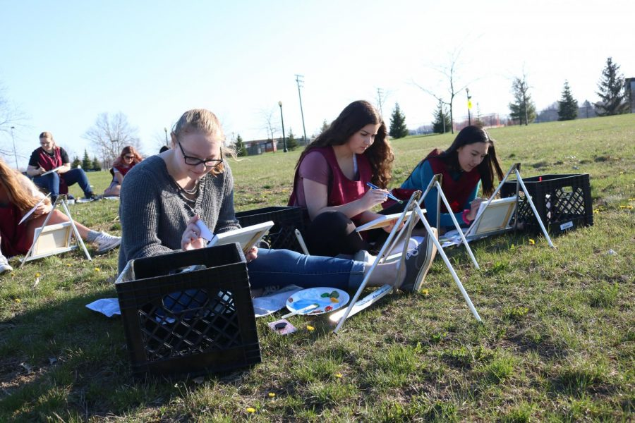 Sophomore Anna Aveandt enjoys the sunny weather outside doing landscape painting on canvas with her art class.