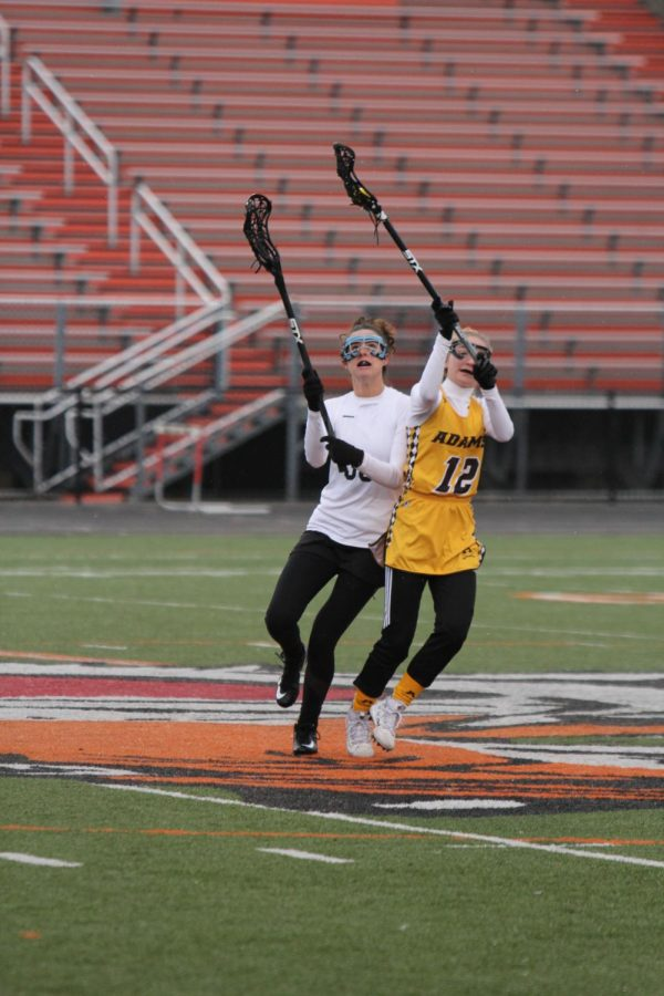 Senior Jessica Lynch loses the draw against Adams offense and is forced to play defense to prevent them from scoring a goal. Girls varsity Flax took a loss 14- 5.