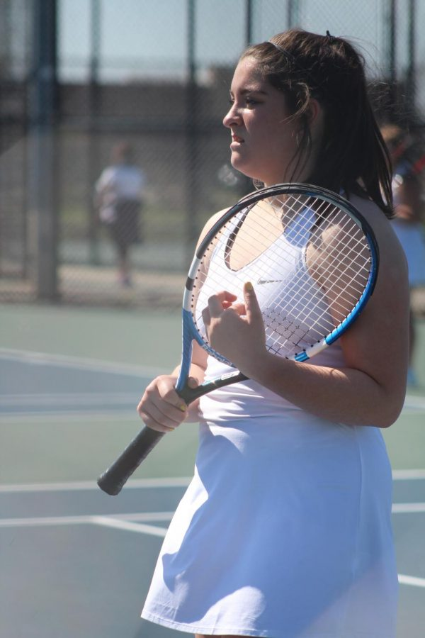 Holding her blue and black tennis racket, senior Leah Krantz focuses her attention on her Owosso tennis rivalry. The Fenton girls varsity won 5-3.