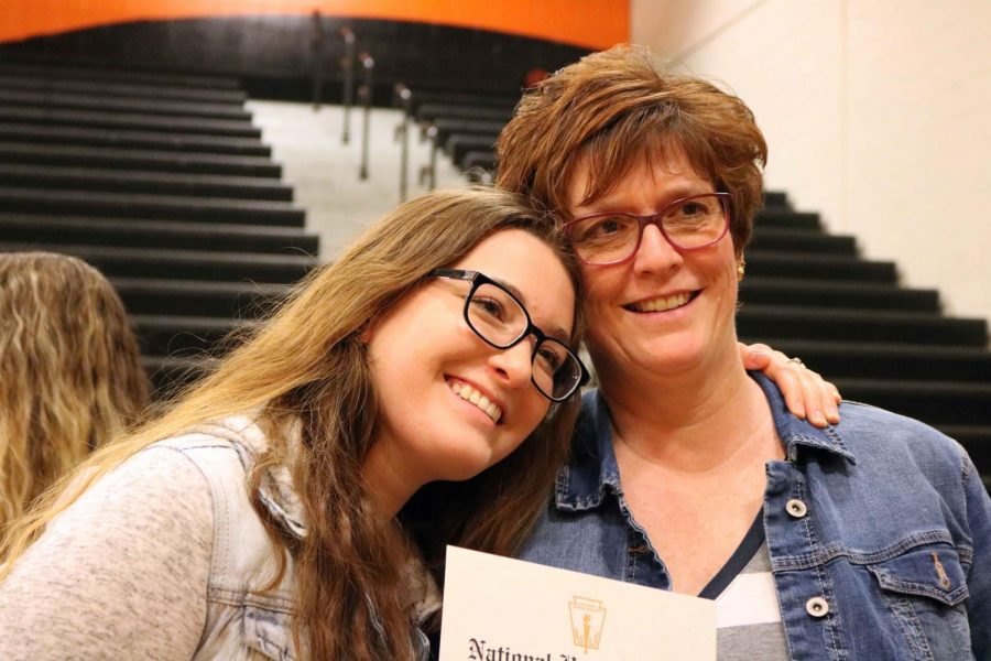 Junior Kyra Schuyler embraces her mom after being inducted into National Honor Society. There were 53 new members this year who were inducted on Apr. 25 in the main gym.