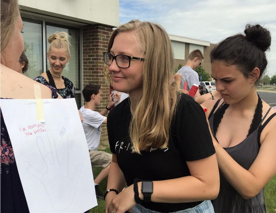 Participating in the senior picnic, sophomore Abby Sizemore smiles as sophomore Regina Pauly writes a compliment on her back. The Fenton InPrint hosted a senior picnic with food and activities as they said goodbye to the seniors.