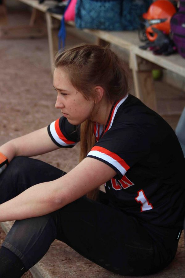 Freshman Ella Turnblom sits in the dugout after being switched out of the pitcher position. The girls softball team was mercied in their game against goodrich with a score of 1-16.