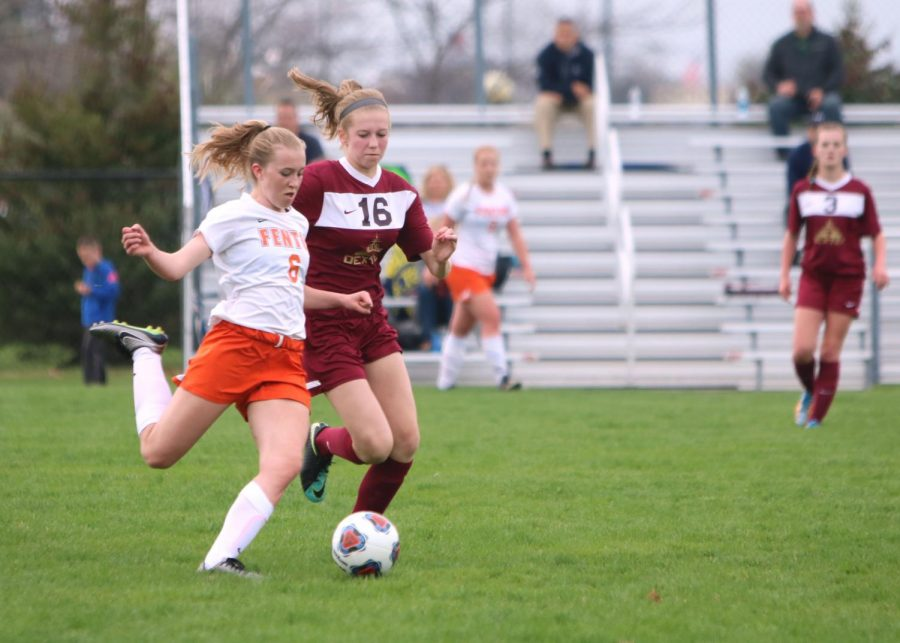 Freshman Mallory Lehmann prepares to kick the ball away from an opposing teammate on May 3. The JV girls soccer team played a game against Dexter.
