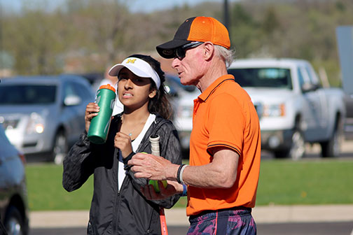 Hydrating after her match, freshman Sarasee Kiran discusses the games with her coach. Kiran and her partner play one doubles for the varsity tennis team.