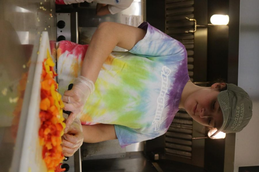 With her army green hat on, junior Jamie Elrod helps the soup kitchen staff by slicing vegetables. The key club members volunteered at the Soup Kitchen in Flint on Saturday the 26.