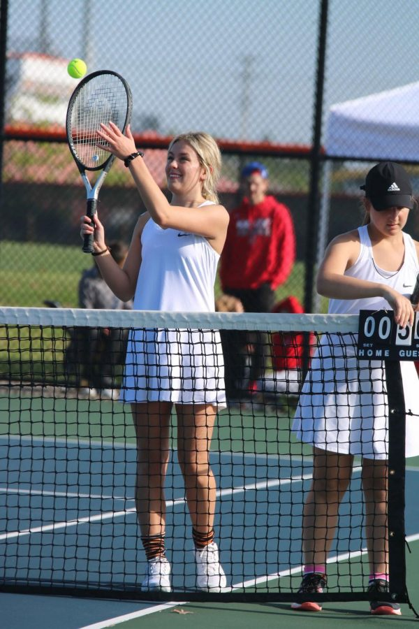 While passing the ball to the opponent, junior Alex Marsee and her partner, sophomore Brooke Kienast update the score for the match on May 23. The girls lost this match against Swartz Creek.