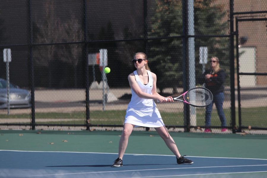 Returning the ball to the opposing player, senior Alyssa Golden plays in her singles match. The girls varsity and JV teams went up against their greatest rivals Holly.