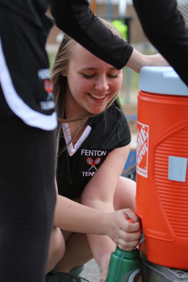 Smiling while filling up water bottles before there game, freshman Liz Donohue prepares for the match against Kearsley. As the warm weather set in, the Fenton JV tennis team fell to Kearsley on April 20th, losing 6-2.