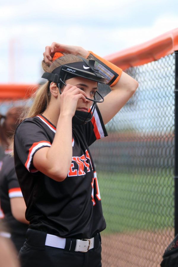 Preparing to pitch, sophomore Anna Weigle puts her face mask on. The girls won their game against Holly on Thursday  9-8.