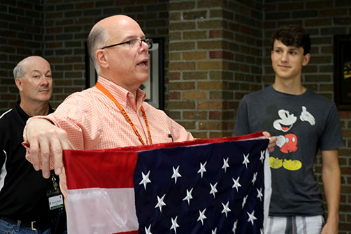 Preparing for the summer, principal Mark Suchowski accepts a new American Flag. The flag will go on the school's flag pole replacing the old one.
