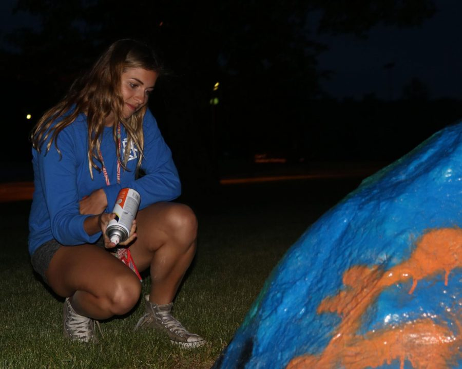 Helping paint the rock, senior Rachael Rittichier takes a look at her work. The seniors painted the rock off of Donaldson Drive in Jackson Gangwer's honor the night before graduation.