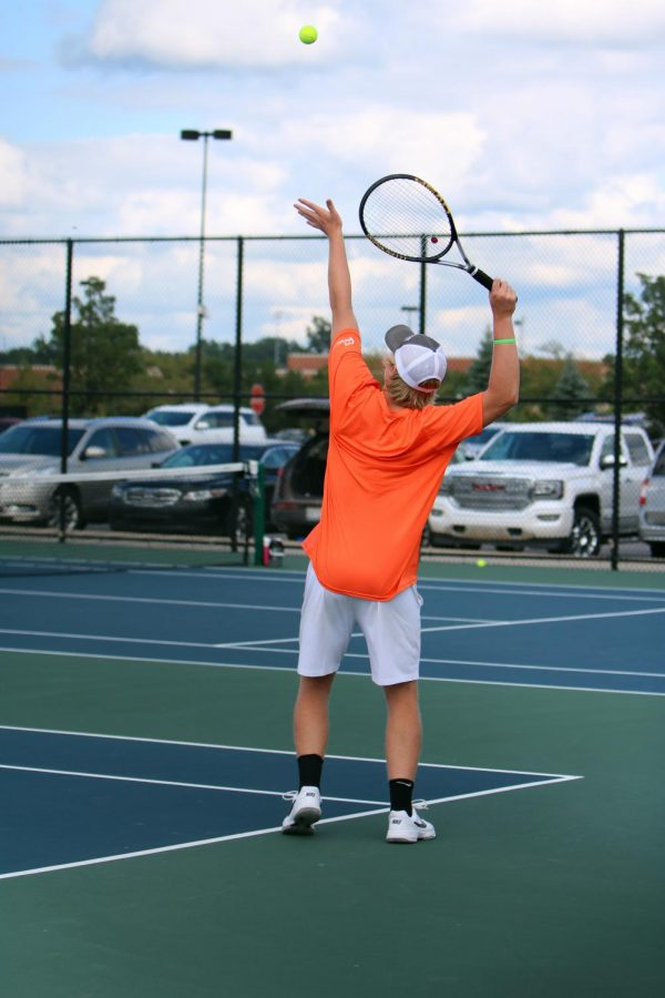 Preparing to serve, junior Jack Gundry, competes in his doubles match against Goodrich. The tennis boys tied up their game with Goodrich on Aug. 30.