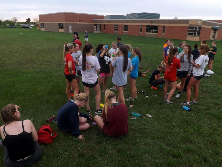 Senior Payton Hurley talks with other seniors as they wait for Powderpuff practice to start. The female juniors and seniors will face off on Sep. 17 at 7 at Fenton High School.