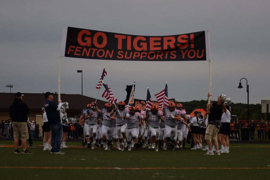 The Fenton Tigers rush the field with pride in preparation to play the Heros Night game. They won their game against Owosso 62-7.