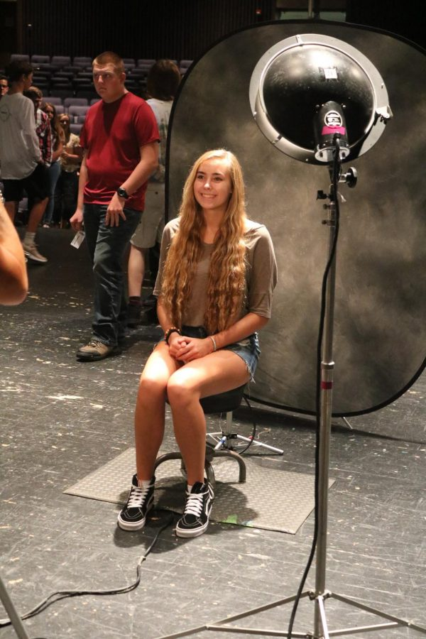 Sitting in front of the camera, junior Ellie Koester smiles as she gets her school photo taken. The students were being photographed for the 2018-19 yearbook.