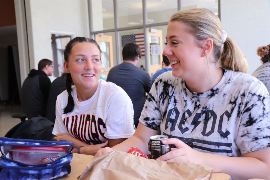 Wearing her powder puff uniform, junior Riley Hurley smiles and laughs with her friend on Sept. 17. Students wore their groutfit clothes while senior and junior girls sported their uniforms for the powder puff game that night.